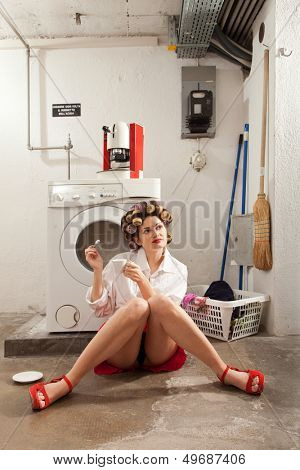 young woman in laundry, she drink coffee