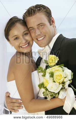Portrait of loving newlywed couple standing cheek to cheek outdoors
