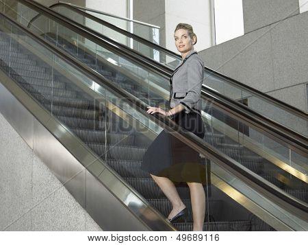 Full length of confident businesswoman standing on escalator