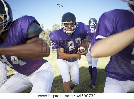 Multiethnic players playing American football on field
