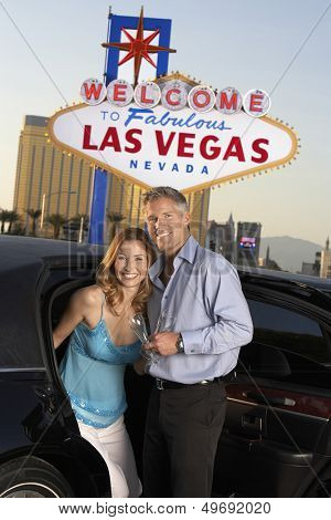 Portrait of happy couple with champagne flutes disembarking from car against Las Vegas sign