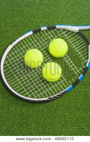 Tennis Concept: Racket With Balls Lies On Green Grass Court