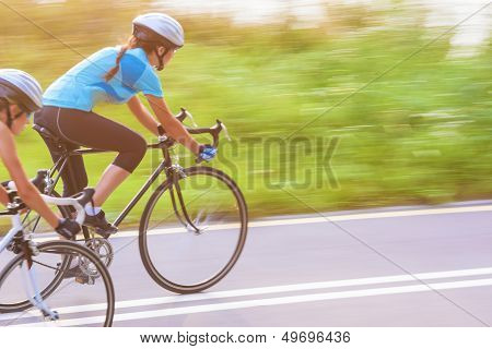 Training Process Of The Two Female Caucasian Sportswomen Riding Sport Bikes Outdoors Horizontal Imag