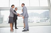 foto of coworkers  - Business people meeting in bright office shaking hands - JPG