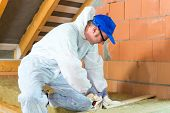 foto of overalls  - Worker in overall is cutting insulating material with gloves and knife - JPG
