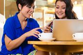 stock photo of internet-cafe  - Asian female friends enjoying her leisure time in a cafe - JPG
