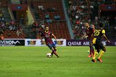 KUALA LUMPUR - AUGUST 10: FC Barcelona's Xavi Hernandez (maroon/blue) controls the midfield in a gam