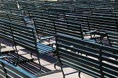 stock photo of patron  - Rows of empty green benches at sports stadium before opening hours - JPG