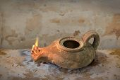 picture of biblical  - Ancient Middle Eastern oil lamp on grunge table - JPG