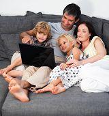 Постер, плакат: Семья на диване с ноутбуком