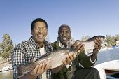 Portrait of happy father and son showing freshly caught fish
