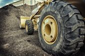 stock photo of wheel loader  - Bull dozer heavy duty construction site focus on large tire - JPG