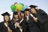 picture of convocation  - Portrait of happy female students with diplomas and balloons standing against sky - JPG