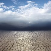 stock photo of surreal  - Beautiful surreal abstract landscape with cobblestones and cloudy sky - JPG