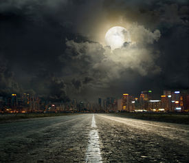 stock photo of moonlight  - asphalt road leading into the city at night - JPG