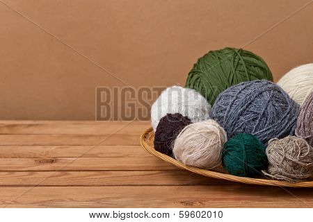 Multicolored Yarn Balls In A Straw Basket On A Wooden Table