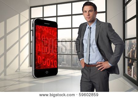 Serious businessman with hands on hips against room with large window showing city