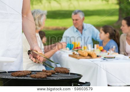 Close-up of barbecue grill with extended family having lunch in the park