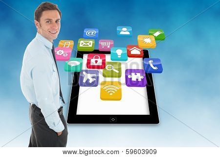 Happy businessman standing with hand in pocket against computer applications