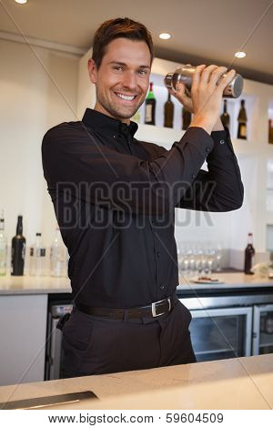 Happy bartender shaking cocktail at the bar