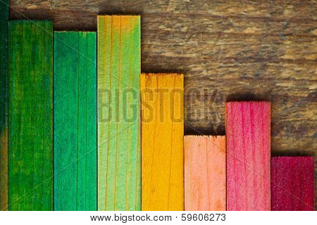 Colorful wood stain color test samples on rough wood. arranged like a bar graph.