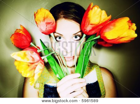 Girl Peeking Out From Behind Plastic Flowers