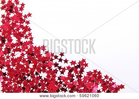 Red stars in the form of confetti on white