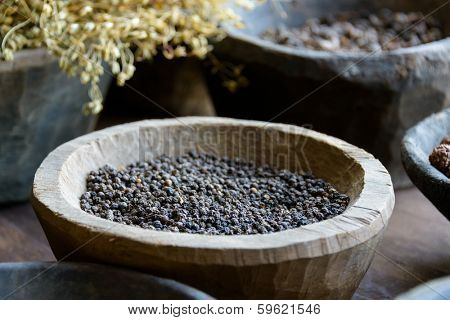 Black pepper in a wooden bowl and other spices and herbs used in ayurvedic medicine