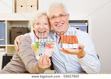 Happy elderly couple with fan of Euro money and little house in their hands