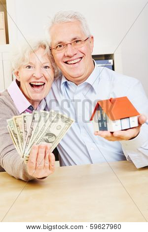 Happy elderly family with dollar bills and a small house
