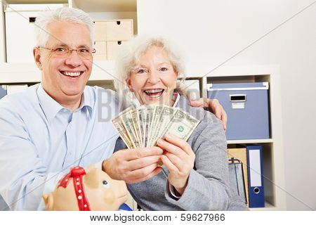 Happy senior couple with fan of dollar bills and a piggy bank