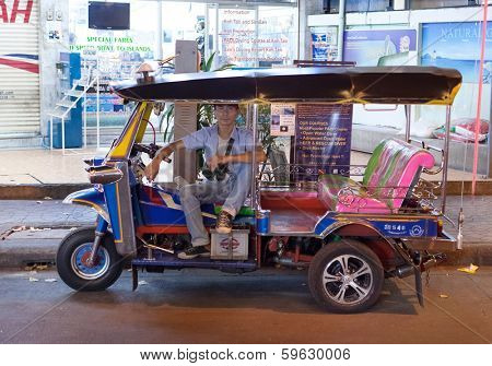 BANGKOK, THAILAND - JANUARY 9, 2012: Local tuk-tuk driver waits for customers. Tuk-tuks have become one of Bangkok's most recognisable transportation features, and are still popular among tourists.