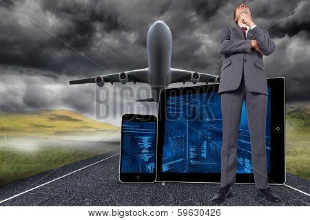 Thoughtful businessman holding pen to chin against 3d plane taking off over street