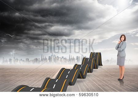 Smiling thoughtful businesswoman against bumpy road backdrop