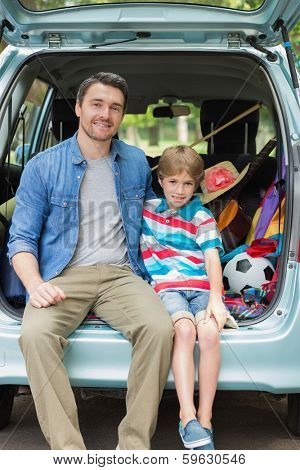 Portrait of a happy father and son sitting in car trunk while on picnic