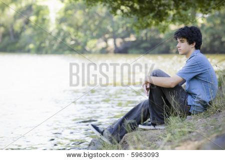 Teen Boy Sitting By Lake