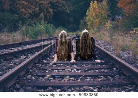 Two Girls Sitting On Railway Tracks And Dream