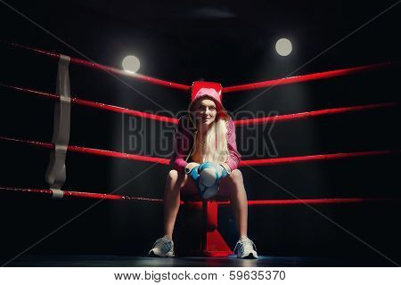 Sports Boxing Woman in box gloves sitting on ring
