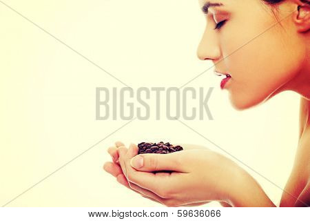 Young woman holding and smelling coffee beans isolated on white