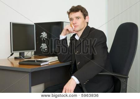 Young Businessman Sits At Table