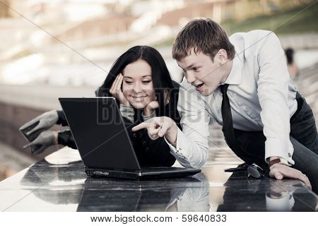 Young business man and woman using laptop outdoor