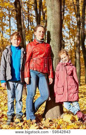 Mother stands with her two children leaning to tree trunk in autumn park