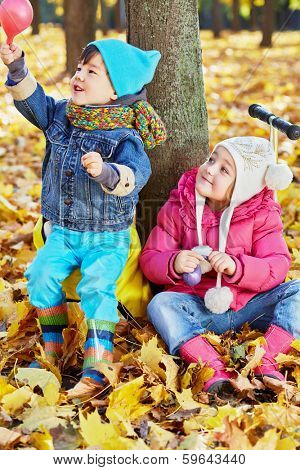 Children sit leaning at tree trunk in autumn park, little boy holds half-deflated air balloon in his hand