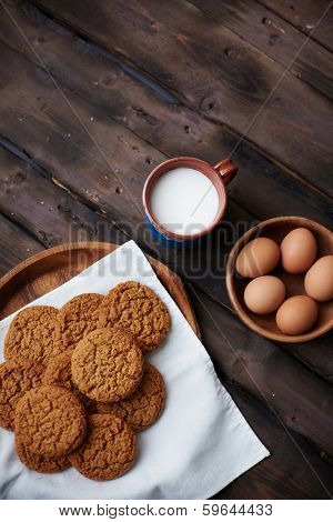 Several eggs in bowl with cup of milk and bisquits near by