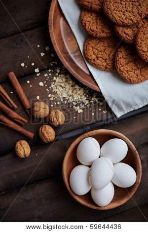 Several eggs in bowl with walnuts, cinnamon, cup of milk and bisquits near by