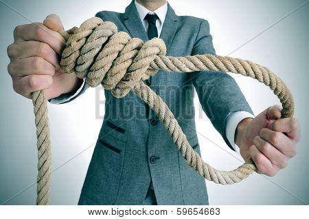 man wearing a suit holding a rope with a hangmans noose