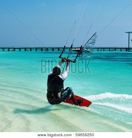 SOUTH ARI ATOLL, MALDIVES - DECEMBER 12 2013: Man kite surfing in waves