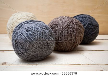 Balls Of Wool On Wooden Table