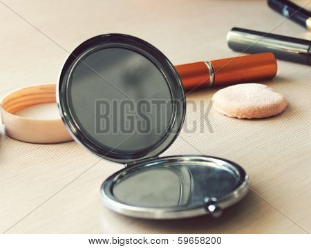 Compact pocket mirror next to powder and a powder puff and other cosmetics