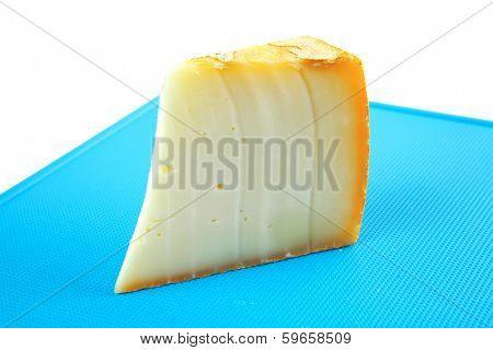 light swiss gouda cheese on blue board